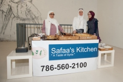 Safaa and ladies to her left and right stand behind table of delicious Arabic food