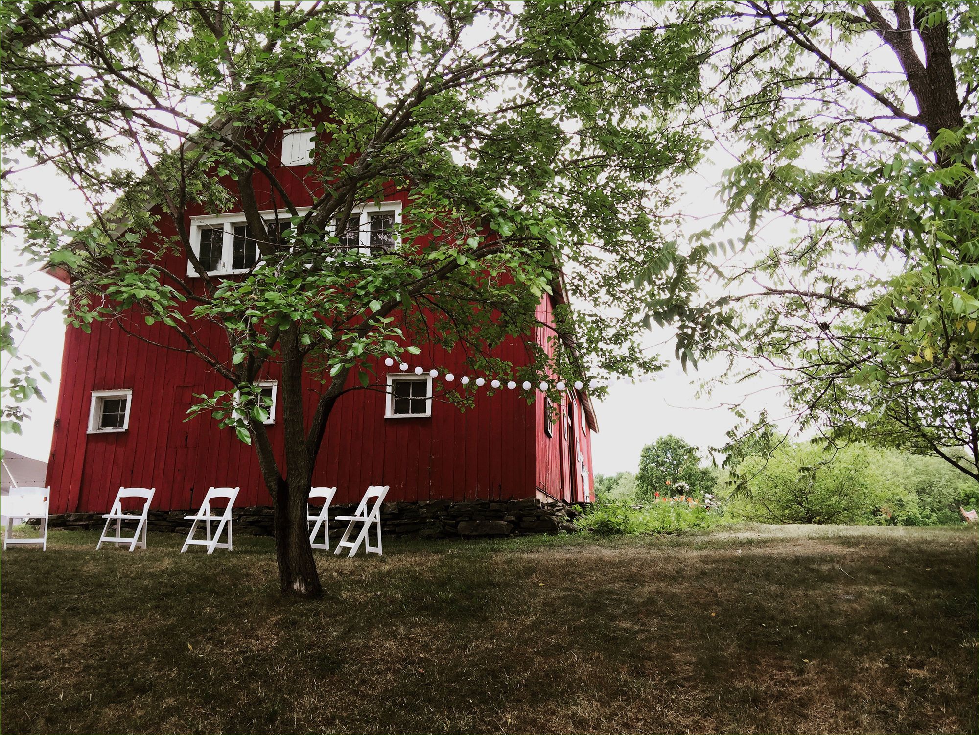 red barn and white chairs - wedding photo by Leyla Sharabi